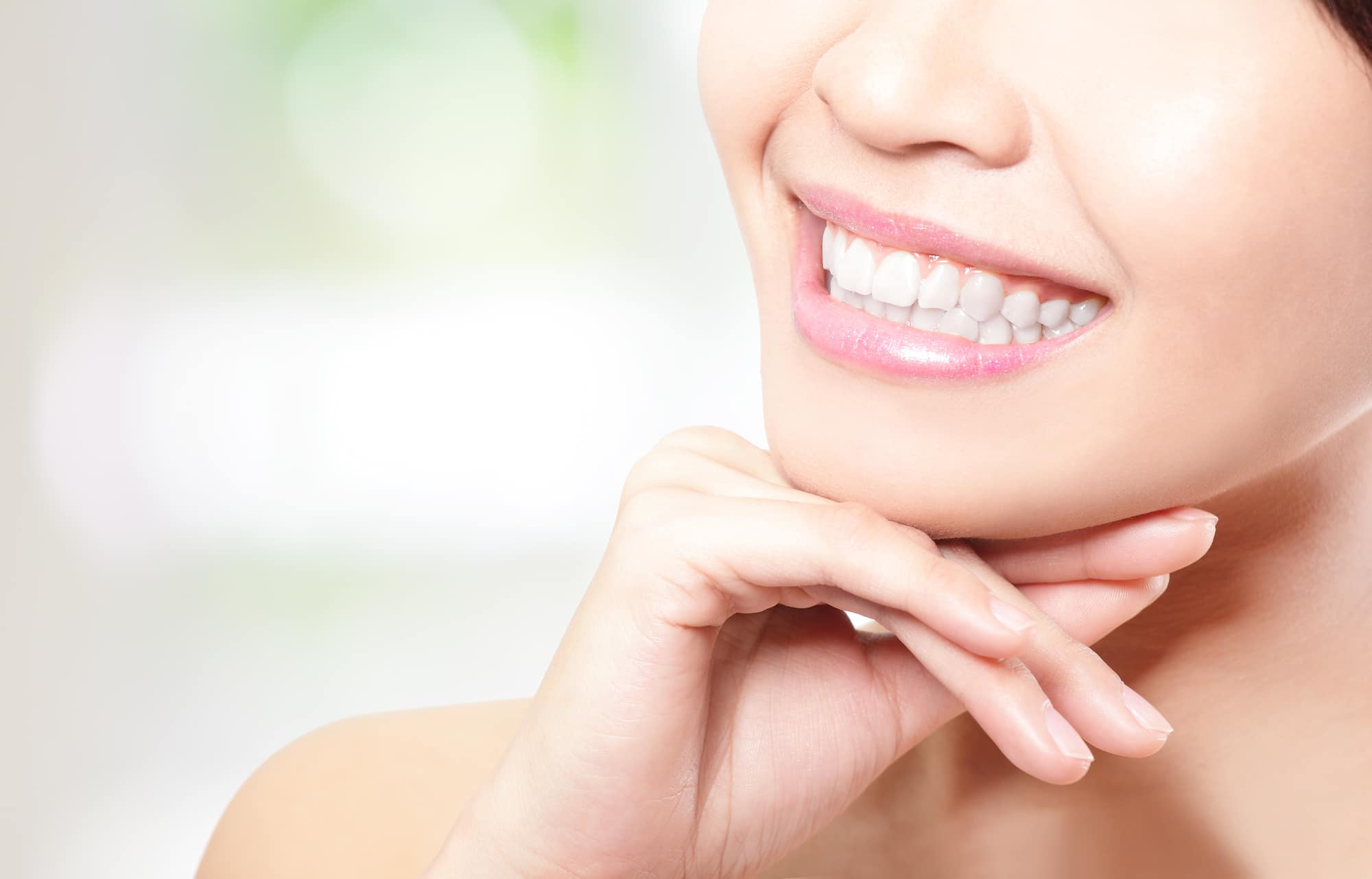 Beautiful young woman teeth close up with copy space on the left side. Isolated over green background, asian beauty model
