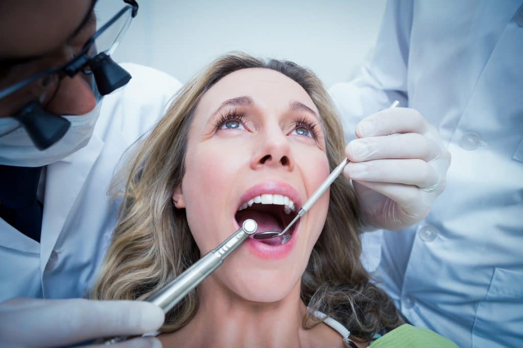 Close up of woman having her teeth examined by dentist and assistant